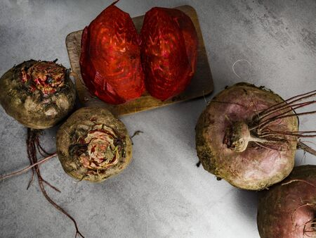 Whole beet root and half on grey background, copy space