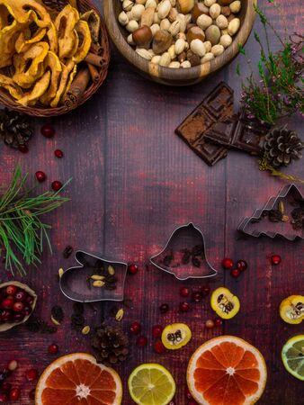 Food background with christmas spices, dried apples, nuts, citrus fruits, cydonia, cranberries, raisin, and baking dish on wooden background. Copy space for christmas recipe. Фото со стока