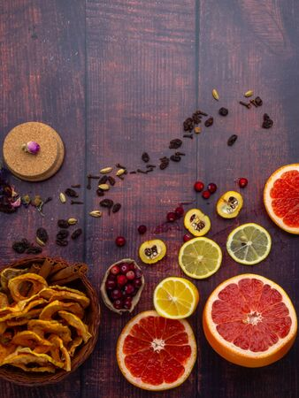 Fall and winter ingredients still life with grapefruits, lemon,cydonia, cranberries, herbs, dried apples, cinnamon sticks, spices, raisin on wooden background, antioxidants, vitamin C rich food, copy space