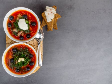 Traditional Ukrainian Russian borscht with olives, dill, garlic, lard on the bowls. Beetroot soup Top view. Traditional Ukraine food cuisine. Copy space