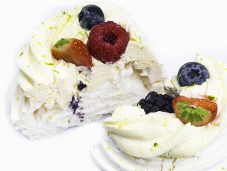 Meringue Pavlova with cream and fresh berries, strawberries, raspberries, blueberries isolated on white, copy space, selective focus