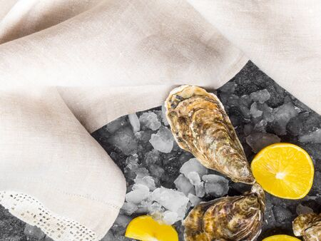 fresh raw oysters on ice with lemon slices, mollusk of the Atlantic Ocean on linen towel Фото со стока