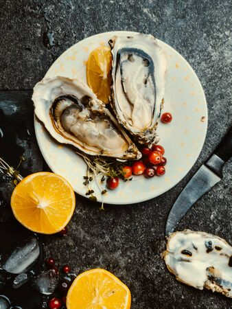 Oysters heart shape in plate with ice, lemon, cranberries, microgreens, knife, shells on marble. Delicacy super food, rich in antioxidants, vitamin, zinc