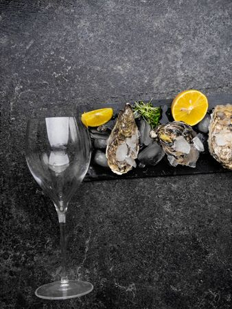 Fresh oysters in ice with lemon with glass for wine or champagne over stone table. Selective focus, Copy space. Top view. Toned