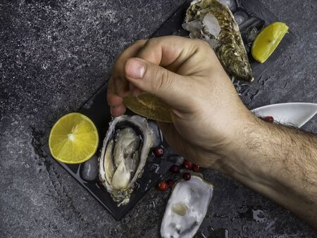 Luxury meal, oysters with cranberries, lemon slices, Man squeezing lemon on fresh oyster, mollusk shells, close up
