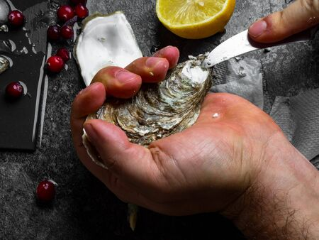 A man with a knife opens a fresh oyster. Dark stone background with lemon, ice, berries, selective focus. Food for men health, rich in protein, iodine, zinc