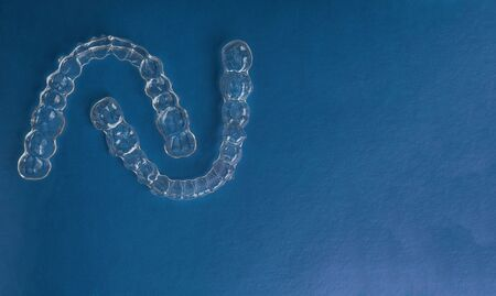 Invisible dental teeth brackets tooth aligners on trendy blue background, Plastic braces dentistry retainers to straighten teeth. Orthodontic temporary removable straighten, copy space