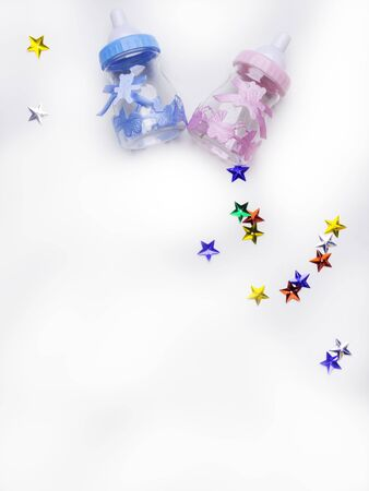 Is it a boy or a girl concept. Blue and pink toy bottles isolated on white, decoration with colorful stars. Twins baby shower. Baby announcement. Flat lay, copy space Reklamní fotografie