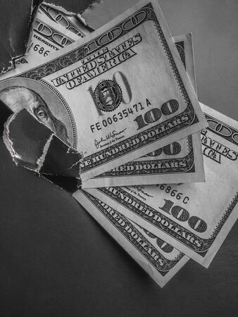 Dollars with Benjamin Franklin bill in a torn hole in black paper. The concept of hidden income tax evasion, donation, profit, corruption, poverty, benefits, scholarships, and generosity Copy space. Monochrome