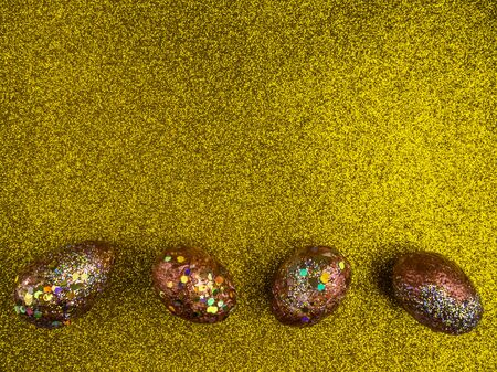 Red golden eggs. A symbol of making money and successful investment on festive gold background, copy space 스톡 콘텐츠