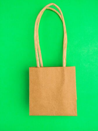 reusable brown paper bag on green background, conservation, Zero waste, eco friendly concept. Flat lay., close up Stock fotó