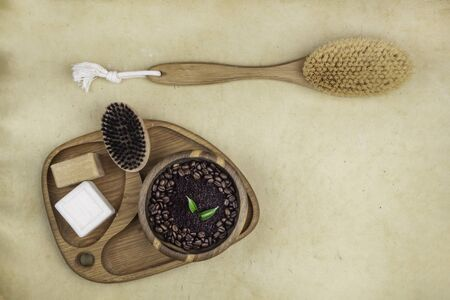 skin care products as pink lotion cream, body brush, coffee scrub for peelin. Body care concept. Close up