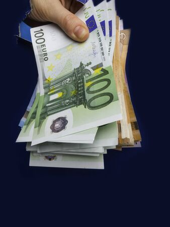 hand appears euro currency inside hole from torn paper, the concept of cash gift, surprise, win, treatment fees, bribes, illegal surgery. Close up 스톡 콘텐츠