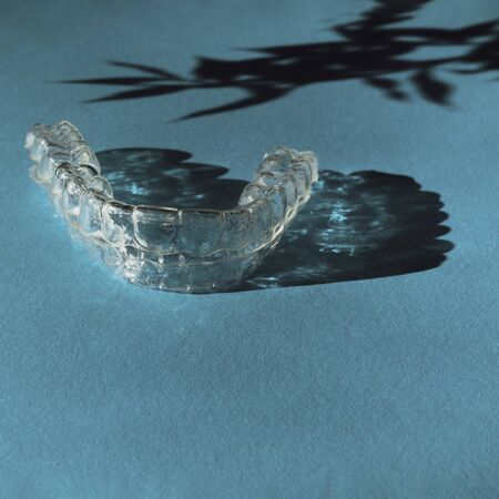 Invisible aligners teeth brackets on blue background with flower shadow