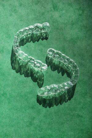 Modern tooth transparent aligners or braces to straighten teeth in cosmetic dentistry and orthodontics on green background, copy space