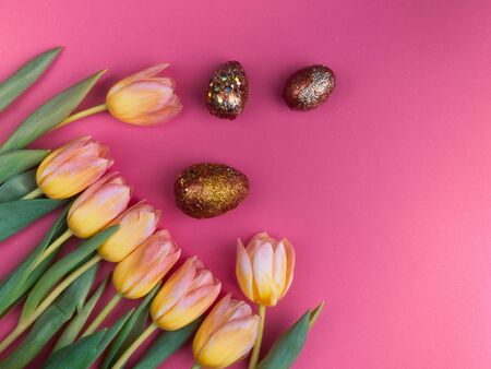 Painted with acrylic paint, decorated with glitters easter eggs with beautiful flowers - yellow tulips on pink background, copy space, top view