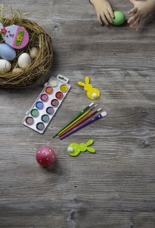 baby hand turn easter egg. In wooden table paints, brushes, bunny, nest. Prepares to paint Easte eggs