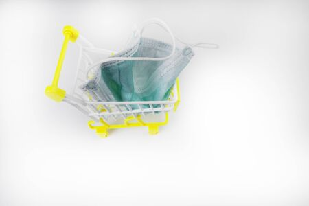 Medical face mask in a shopping cart, trolley on white background, personal protective and pharmacy online shopping concept