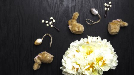 chocolate willow branches and cute bunnies with eggs, narcissus flowers on black wooden background, happy Easter greeting card, spring festive season. Flat lay, top view