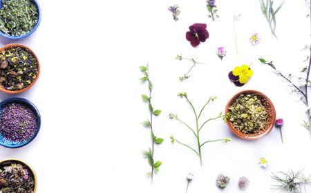 assortment of mixed fragrant dry flowers and variety herbals tea in ceramic bowls isolated on white. Herbal medicine, homeopathy and herbal tea for health, top view, selective focus