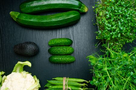 Variety of green vegetables on wooden background, broccoli, avocado, micro sprouts, peas, salad, zuchini, cucumber, cauliflower, cabbage, flat lay. Detox healthy food
