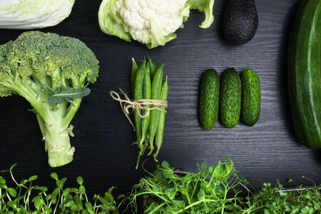 Variety of green vegetables on wooden background, broccoli, avocado, micro sprouts, peas, salad, zuchini, cucumber, cauliflower, cabbage, flat lay. Detox healthy food, Source of protein for vegetarians. Clean eating