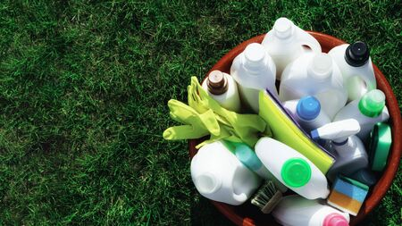 Cleaning variety supplies, group of colorful plastic bottles outdoor, Basket with cleaning items