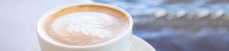 banner of blurred white cup with art coffee in sea background, with gradient, copy space