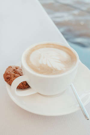 White art latte or cappuccino coffee cup with a single chocolate cookie