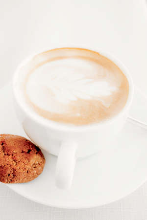 White art latte or cappuccino coffee cup with a single sweet chocolate cookie