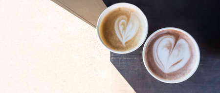two cups of coffee cappuccino and latte or chocolate with heart shaped art, on wooden table, top view, copy space. Love coffees on a rustic wood table 版權商用圖片