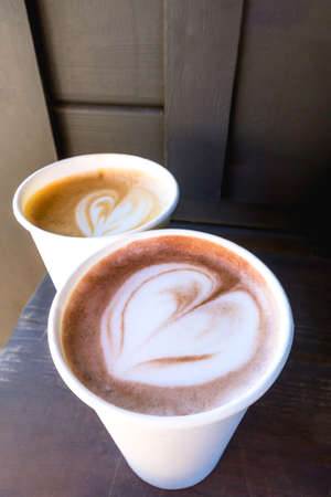 two cups of coffee cappuccino and latte heart shaped art on wooden table, top view, copy space. Love coffees on a rustic wood table