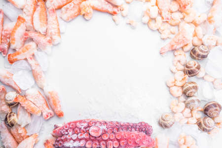 assortment of frozen seafood on ice cubes, shrimps, octopus, Babylonia areolata shellfish snails, langoustines, rich in iodine, antioxidants and vitamin, top view, copy space Stock Photo