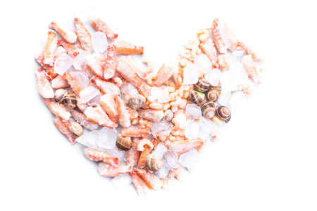assortment of frozen seafood on ice cubes, shrimps, Babylonia areolata shellfish snails, langoustines, rich in iodine, antioxidants and vitamin, top view, copy space Stock Photo