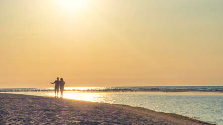 couple silhouette of two people in love at sunset, relaxed man and women walking and enjoying sunset beauty