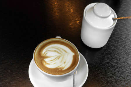 Cup of hot latte or cappuccino art coffee in white cup with beautiful foam, place for text