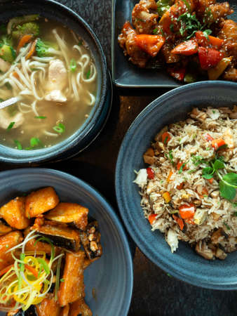 various traditional Chinese or indian cuisine meal food, vegan or vegetarian restaurant dishes, chicken soup, rice, eggplant, in ceramic bowls. Assortment of Healthy eastern local food. Selective focus