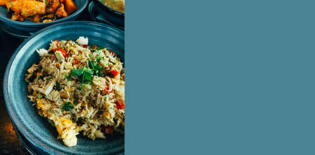 Chinese cuisine, fried rice with egg omelet, mushrooms and vegetables, rice dish of fried rice in vintage ceramic blue bowls, thai menu, selective focus