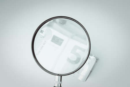 magnifying glass on 50 Euro cash banknotes. European money, fake money, currency, debt, economy and financial analysis concept.