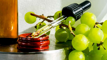 Grape seed oil in a glass bottle with ripe green grape, oil dripping in pipette. Pure essential skin care oil. Alternative medicine or Spa treatment concept. Selective focus. Copy space