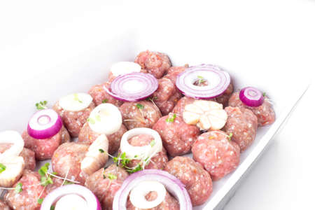 homemade raw organic mincet meat balls with onion, garlic, micro greens, uncooked, isolated on white, close up. Chinese food. Macro Stock fotó