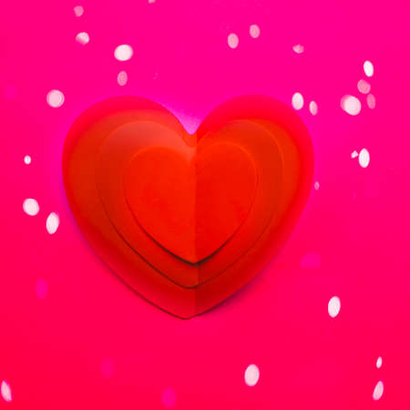 Background with one paper heart origami, Valentine greeting card or Happy Valentine's Day with lights, love concept. Handcrafted designed card expressing love.