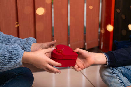 Close-up girl hands taking present heart shaped box from his boyfriend. Valentines Day and Sweetest day. Happiness moment concepts Love and presents with festive magic lights Stock fotó