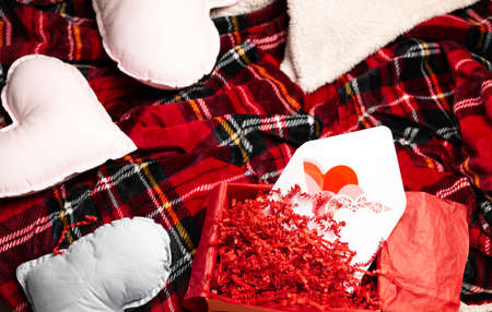 Red hearts on soft cozy plaid. Valentines Day holiday concept