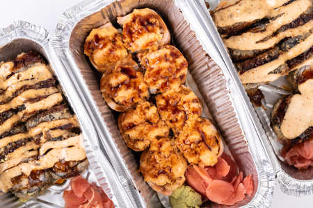 hot delicious sushi roll with grilled cheese, mayonnaise packaging in foil aluminum box container for Japanese food delivery, airplane or Takeaway selection menu.
