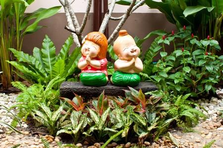 Tradition Thai children ceramic dolls decoration in the garden photo
