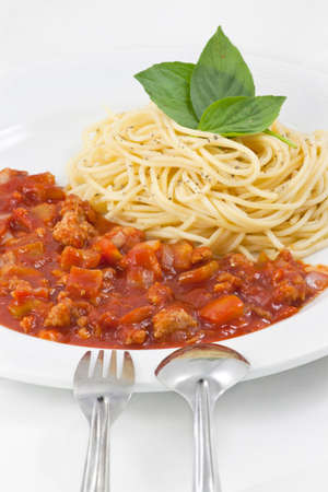 Spaghetti with sauce in plate with fork and spoon photo