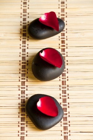 hot rock therapy: Hot mineral stones in spa with red rose petal