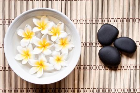 relaxation background: Plumeria and hot mineral stone in spa Stock Photo