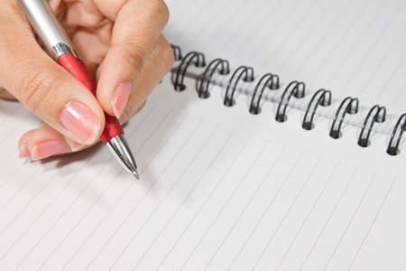 Hand with pen going to write something in notebook Stock Photo - 9447232